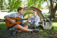 Homme mignon chantant une sérénade à son amie sur des vacances en camping Image libre de droits