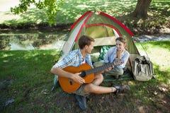 Homme mignon chantant une sérénade à son amie sur des vacances en camping Photographie stock