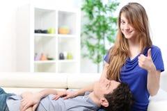 Homme mignon rallongé sur les cuisses de son amie sur un sofa Images stock