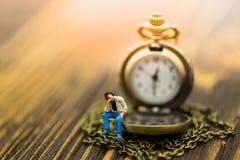 Homme miniature s'asseyant sur l'horloge Utilisation d'image pour passer des minutes précieuses chaque minute ensemble Image stock