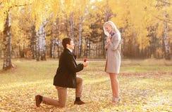 Homme mis à genoux proposant l'anneau à une femme en automne photo stock