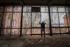 Homme mis en cage dedans à un composé abandonné image libre de droits