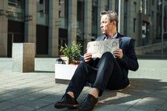 Homme mis le feu se sentant embarrassé tout en se reposant sur le plancher dehors photographie stock libre de droits