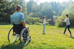 homme Mobilité-altéré observant sa famille jouer avec la boule Image stock