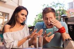 Homme moderne riant bruyant tout en observant de vieilles photos Photos libres de droits