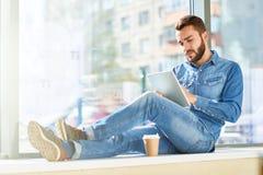Homme moderne travaillant à la fenêtre ensoleillée Photographie stock libre de droits