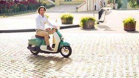 Homme montant un scooter en ville Photos stock