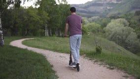 Homme montant un scooter ?lectrique en parc banque de vidéos