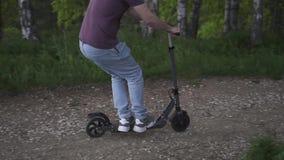 Homme montant un scooter ?lectrique en parc clips vidéos