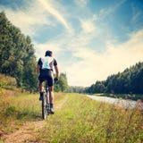 Homme montant une bicyclette sur le fond de nature Image stock