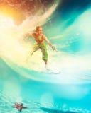 Homme montant une planche de surf sur une vague Photos stock