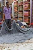 Homme montrant des tapis dans un magasin Image stock