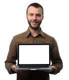 Homme montrant l'ordinateur portable avec l'écran vide photographie stock
