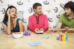 Homme montrant la main de gain aux amis tout en jouant des cartes Images stock