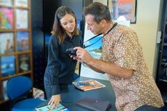 Homme montrant la photographie d'agent de voyage sur l'appareil photo numérique Photographie stock libre de droits