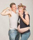 Homme montrant le biceps à la femme enceinte image stock
