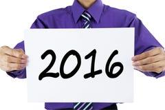 Homme montrant les numéros 2016 sur le papier images libres de droits