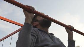 Homme motivé faisant traction-UPS sur la barre transversale extérieure, activité de sports, au ralenti banque de vidéos