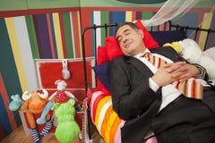 Homme mûr dormant dans le bâti d'enfant Images libres de droits