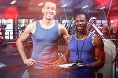 Homme musculaire avec l'entraîneur souriant à l'appareil-photo images libres de droits