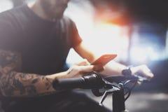 Homme musculaire barbu tatoué en tenant des mains de smartphone et en employant l'appli de cartes avant la monte en le scooter él image stock