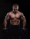 Homme musculaire bel établissant avec des haltères Photos libres de droits