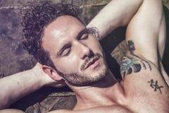 Homme musculaire bel sur la plage s'étendant sur des roches images stock