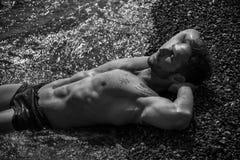 Homme musculaire bel sur la plage s'étendant sur le gravier Photographie stock libre de droits