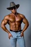 Homme musculaire bel utilisant un chapeau et des lunettes de soleil image libre de droits