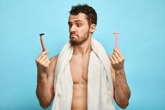 Homme musculaire confus émotif tenant deux rasoirs images stock