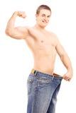 Homme musculaire convenable dans une grande paire de jeans montrant son biceps Images libres de droits