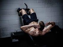 Homme musculaire faisant des exercices pour abdominal dans le gymnase Photo stock