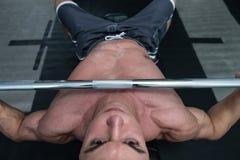 Homme musculaire faisant l'exercice de banc à presse pour le coffre Photographie stock