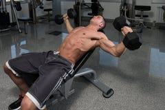 Homme musculaire faisant l'exercice pour le coffre avec des haltères Images libres de droits