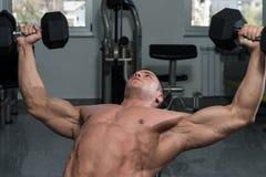 Homme musculaire faisant l'exercice pour le coffre avec des haltères Image stock