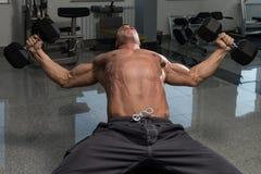 Homme musculaire faisant l'exercice pour le coffre avec des haltères Photos stock