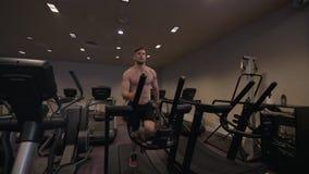 Homme musculaire faisant la cardio- formation sur le tapis roulant dans le mouvement lent de club en bonne santé images libres de droits