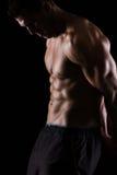 Homme musculaire intense posant sur le noir photo libre de droits