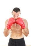 Homme musculaire sérieux avec les gants de boxe rouges reliés près de son f Photographie stock