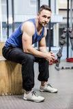 Homme musculaire s'asseyant sur le bloc en bois images stock