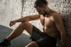 Homme musculaire se reposant après séance d'entraînement de gymnase photographie stock libre de droits