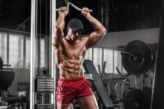 Homme musculaire sexy établissant dans le gymnase faisant des exercices, ABS nu masculin fort de torse Photos stock
