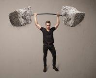 Homme musculaire soulevant de grands poids de pierre de roche photographie stock