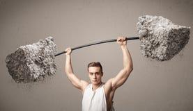 Homme musculaire soulevant de grands poids de pierre de roche Photographie stock libre de droits