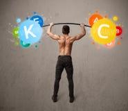 Homme musculaire soulevant les poids colorés de vitamine images libres de droits