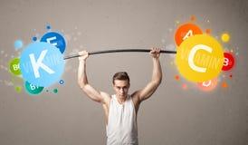 Homme musculaire soulevant les poids colorés de vitamine photographie stock libre de droits