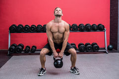 Homme musculaire soulevant un kettlebell Photo stock