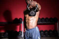 Homme musculaire soulevant un kettlebell Images stock