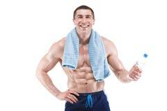 Homme musculaire souriant avec la serviette bleue au-dessus du cou, eau potable, d'isolement sur le fond blanc Photographie stock libre de droits