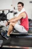Homme musculaire sur la machine à ramer souriant à l'appareil-photo photographie stock